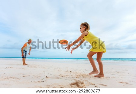 Father and daughter playing with flying disk at beach - stock photo