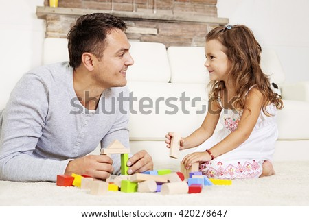 Father and daughter playing with wooden blocks on the floor. - stock photo