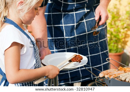 Father and daughter preparing meat and sausages using a barbecue grill - stock photo