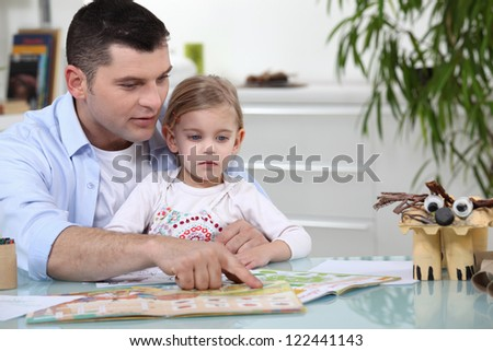 Father and daughter reading together - stock photo