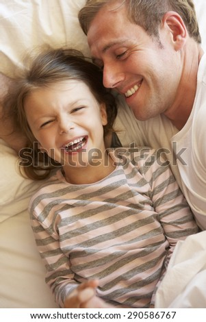 Father And Daughter Relaxing In Bed - stock photo
