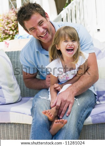 Father and daughter relaxing in garden - stock photo