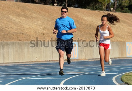 Father and daughter running on a blue racetrack - stock photo