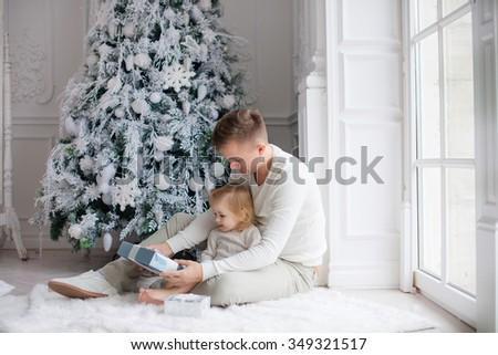 father and daughter sitting near the Christmas tree and Christmas gifts watch - stock photo