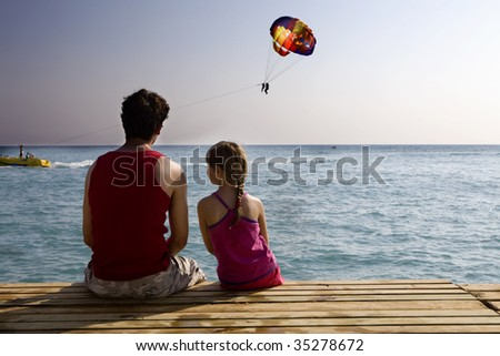 father and daughter sitting together on piers and looking at sea - stock photo