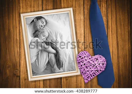 Father and daughter sleeping on bed against wooden background - stock photo