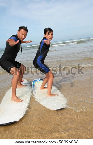 Father and daughter surfing in the ocean - stock photo