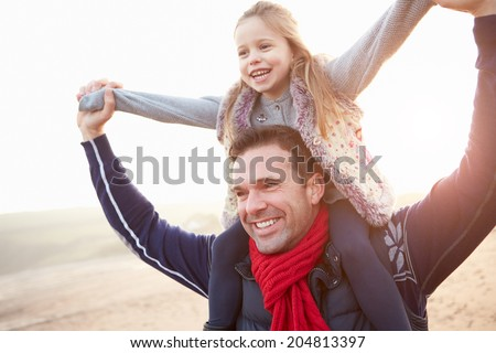 Father And Daughter Walking On Winter Beach - stock photo