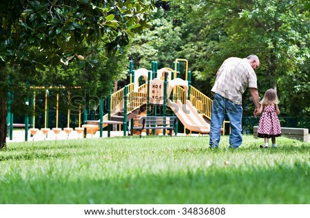 Father and daughter walking to the playground on a sunny day. - stock photo