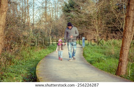 Father and daughter walking together holding hands over a wooden pathway into the forest - stock photo