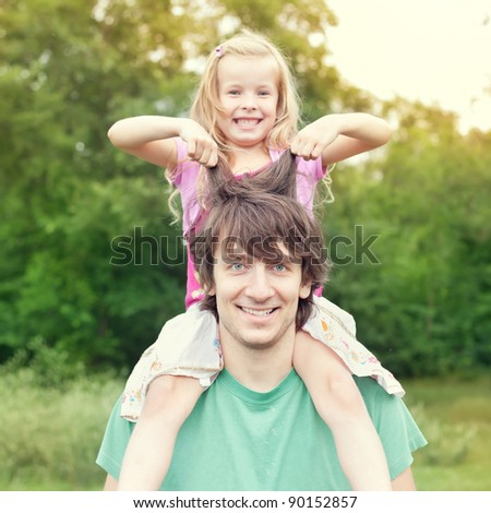 father and daughter.Young man holding blonde little girl on shoulders in park in summer - stock photo