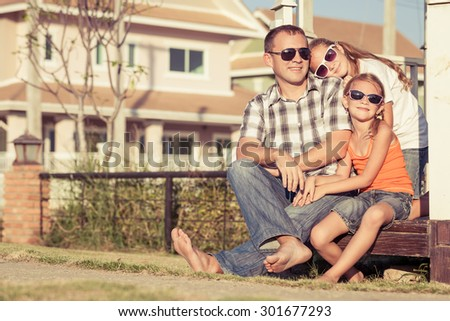 Father and daughters playing near the house at the day time. They sit in the white gazebo. Concept of friendly family. - stock photo