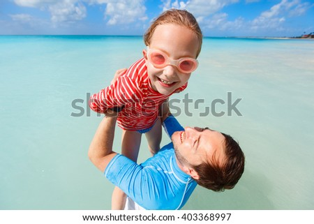 Father and his adorable little daughter having fun splashing in ocean water during summer beach vacation - stock photo