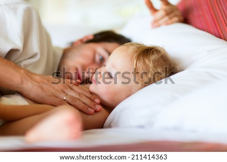Father and his adorable toddler daughter relaxing in bedroom - stock photo