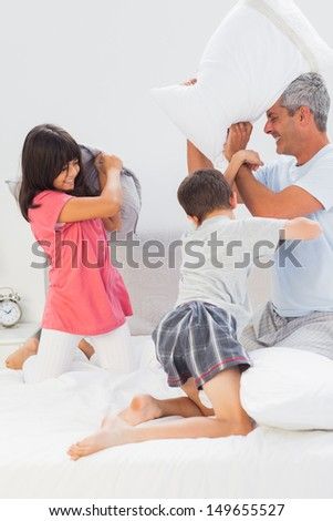 Father and his children fighting together with pillows on bed at home - stock photo