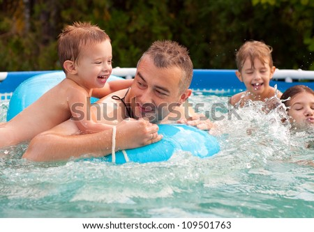 Father and his children having fun in the swimming pool on beautiful summer day. - stock photo