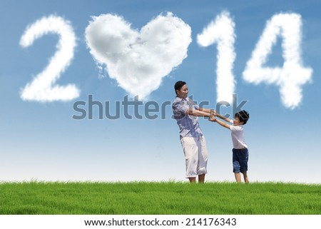 Father and his daughter enjoying new year holiday in the park - stock photo