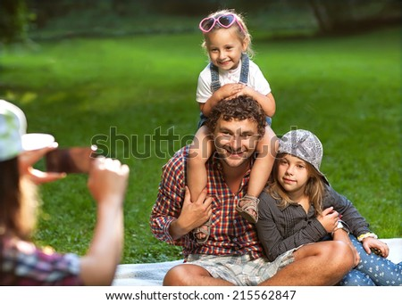 Father and his 3 daughters lie on the grass in sunglasses happy. Photographed, Self - stock photo