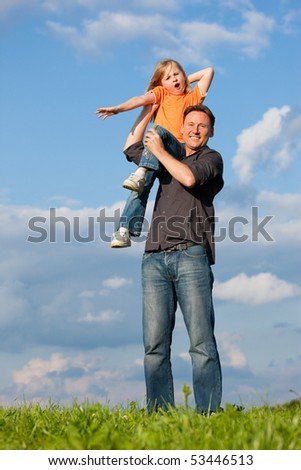 Father and his kid - daughter - playing together at a meadow, he is carrying her on his shoulders - stock photo