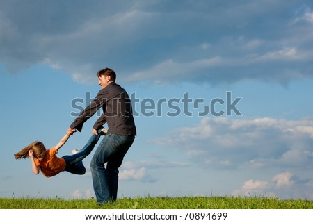 Father and his kid - daughter - playing together at a meadow, he is tossing her around - stock photo