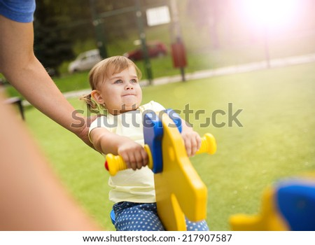 Father and his little daughter playing on playground. - stock photo