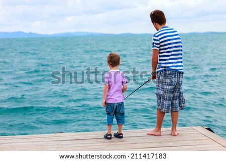 Father and his little son fishing together from wooden jetty - stock photo