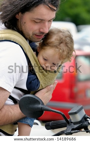 father and his little son in sling look together at motorbike - stock photo