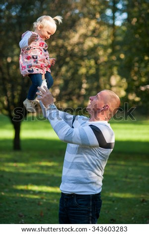 Father and his one year old daughter are having a great time in the park on a sunny day. - stock photo