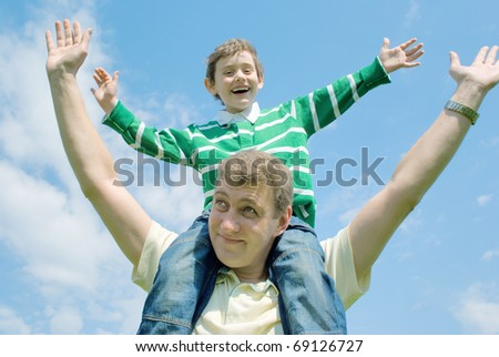 Father and his son against the blue sky with clouds - stock photo