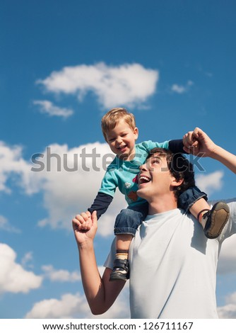 Father and his son against the cloudy sky smiling - stock photo