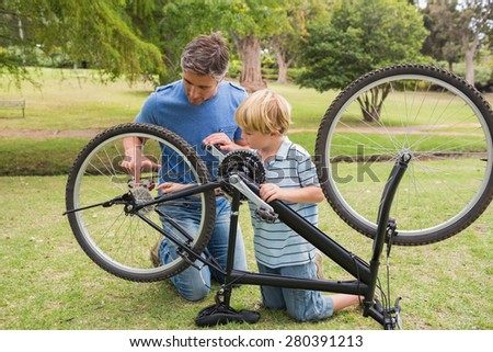 Father and his son fixing a bike on a sunny day - stock photo