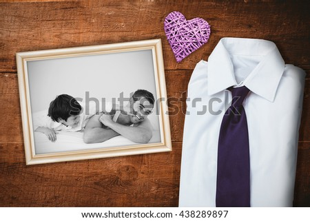 Father and his son having fun on a bed against overhead of wooden planks - stock photo
