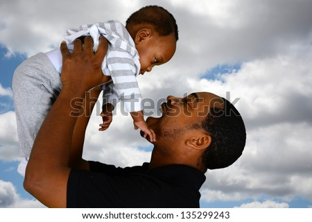 Father and his son playing outside with clouds - stock photo