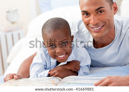 Father and his son reading on bed - stock photo