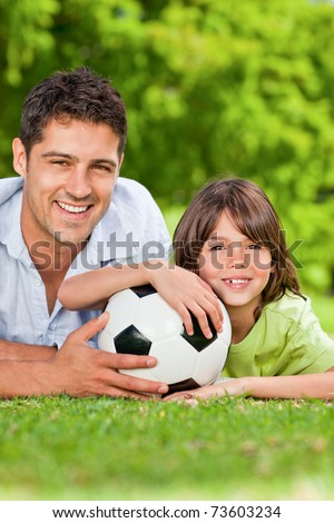 Father and his son with their ball in the park - stock photo