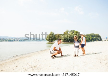 Father and his sons enjoying free time together on the beach - stock photo