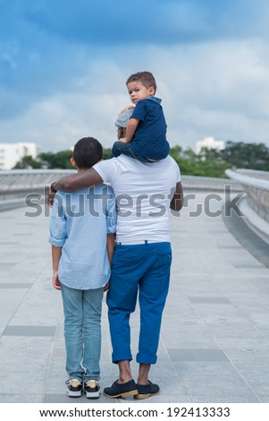 Father and his sons, view from the back - stock photo