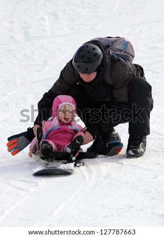 Father and his toddler daughter sliding on snowboard - stock photo