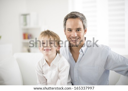 Father and his young son smiling on a couch - stock photo
