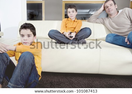Father and identical twin sons watching tv in the living room at home. - stock photo