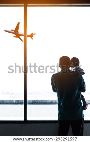 Father and is baby in airport with airplane on background. - stock photo
