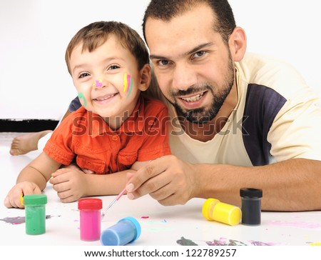 Father and kid playing with paint colors - stock photo