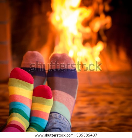 Father and kid's feet in Christmas socks near fireplace. Family relaxing at home. Winter holiday concept - stock photo