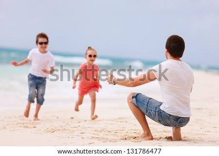 Father and kids enjoying beach vacation - stock photo