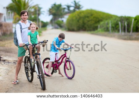 Father and kids riding bikes on sandy road - stock photo