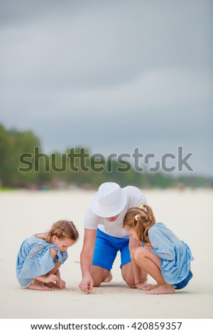 Father and kids walking on white sand beach - stock photo