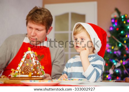 Father and little child preparing a gingerbread cookie house. Family celebrating together traditional Christmas. - stock photo