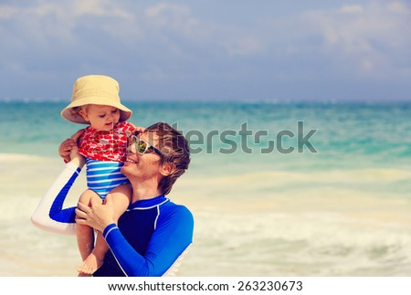 father and little daughter fun on summer beach - stock photo