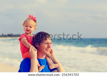 father and little daughter on summer beach vacation - stock photo