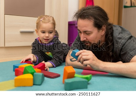 Father and little daughter playing with bricks - stock photo